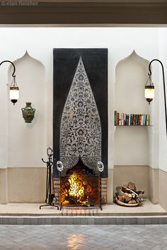 A pair exotic niches with lanterns on either side of Moroccan chiseled tile fireplace Marrakech and Riad Farnatchi Morocco