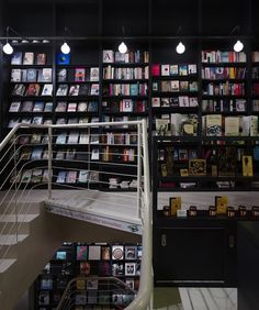 Lutyens & Rubenstein, London bookshop in Notting Hill, book sculptures hanging from ceiling, black book shelves, modern globe pendants, staircase with white railings