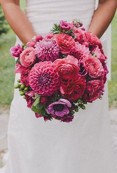 bouquet of dahlias, anemones, ranunculuses, gomphrena, hypericum berries, and geranium leaves