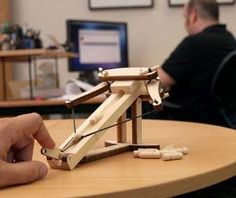 Your office cubicle will never again fall under foreign attack thanks to the mini ballista launcher. It's a decorative yet functional launcher that takes up little space while providing loads of fun. The mini ballista launcher takes the flawless design perfected by past ancient civilizations to bring you the missile hurling capabilities your work staple…