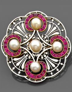A ruby, natural pearl, gold and platinum brooch circa 1910. A brooch designed as openwork florets, embellished with pearls, each framed by calibré-cut rubies, mounted in 18k white gold.