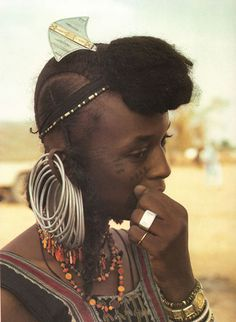 Africa |  Wodaabe women shave their hairlines to increase the length of their faces and enhance their beauty.  In traditional Fulani style they bunch their hair into a large topknot over the forehead. Her hairpin is typical of the Tuareg silver craftsmanship. |  © Angela Fisher, 1987