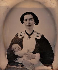 Though the young woman in this ambrotype from the 1850s has a tired look in her eyes (quite understandable given the newborn nestled in her arms!), there's also a clear sense of maternal joy and pride there, too.