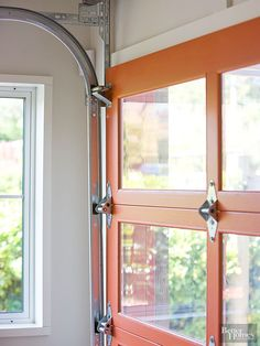 The centerpiece of the converted guest quarters is the original garage door, which was painted a cheery orange color. The clear glass panes offer a connection between inside and outside. For garage spaces converted into living spaces, look for doors that rely on clear panes to let in natural light.