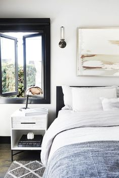 Bedroom with a muted color palette, retro sconces, and a white nightstand