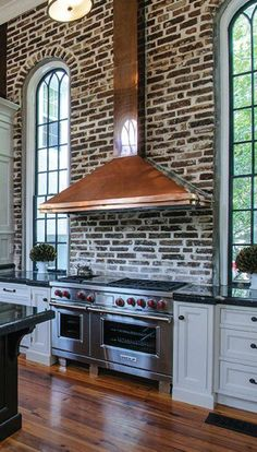 Brick wall, arched windows, wood floor, copper hood and an amazing stove. - Model Home Interior Design Casa Loft, Classic Kitchen, Exposed Brick, Beautiful Kitchens, Kitchen Dining, Kitchen Island, Copper Kitchen, Kitchen Brick, Loft Kitchen