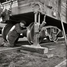 """November 1942. """"Chicago, Illinois. Jacking up a car on the repair tracks at an Illinois Central Railroad yard."""" Someone get the spare out of the trunk? Medium-format negative by Jack Delano, Office of War Information."""