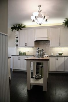 black white kitchen with small butcher block island.