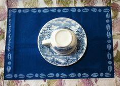 Jogo americano em brim azul cobalto com bordas em algodão cru com desenhos exclusivos de estamparia com carimbos. A Coleção Nanã Buruku é inspirada nas cores, instrumentos e na magia dos orixás.    Ref. 176