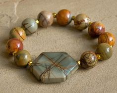 """12mm red creek jasper beads and gold plated beads make this bracelet the perfect accessory for fall. Bracelet is approximately 7"""" in length. Coordinating necklace sold separately."""