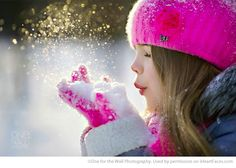 Little girl blowing snow in winter. Love how the sun lights up the snowflakes! Also love the bright pop of color.