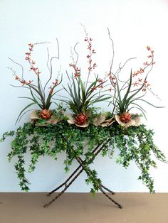 Artichoke, orchid & mushroom arrangement with English ivy. Designed by Arcadia Floral & Home Decor.