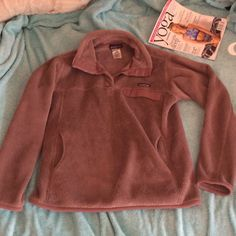 PATAGONIA SNAP-T FLEECE Gently PRELOVED Patagonia snap-t fleece in a size LARGE! Great oversized fit and oh so warm and soft!!! The color is like a light lavender! Totally hard to come by and rare! No major flaws to point out except for the inner tag is slightly torn, but that doesn't bother the look of the wearing of this awesome fleece! Patagonia Sweaters