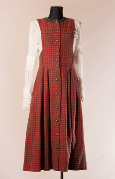 Nice green red checkered dirndl dress. The dirndl dress is button down, there are faux bones buttons. Top part is lined with dark green acetate lining. The dirndl has also pocket on each side. The fabric is tagged as 50% cotton, 35% viscose, 15% linen , there is written Salzburger dirndl look, trachtenecht, Austria. Also, bear in mind that this dress could not be worn together with short cropped dirndl blouses or without any top /blouse, because it is quite cut out itself on the sides. There…