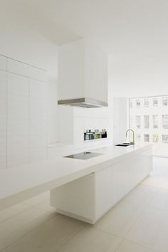 Large white floor tiles, white walls, and high gloss cabinetry, make this dreamy modern kitchen a modern minimalist space.