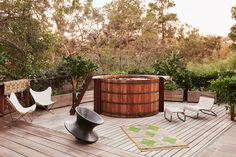 The wooden hot tub, filled with oxygenated and alkalized water, came with the house; Bacon added the butterfly chairs and the Thomas Heatherwick–designed Spun chair.