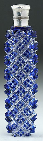 c.1890 Blue Overlay Cut Crystal Scent Perfume Bottle, Silver Top. slim oval form blue overlay crystal scent bottle, with a hinged silver top, silver collar, and glass stopper. The front and back of the body are cut to clear with a pattern of geometric squares, the sides with ovals. $520 USD