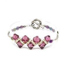 The Amethyst Swarovski Crystal Bracelet radiates with the richness of its deep purple amethyst Swarovski crystals. Its as delightful to wear and perfect for any occasion. From her anniversary to her birthday or graduation it will complement any event. The gorgeous Amethyst Swarovski Crystal Bracelet is made with rich 8 mm purple amethyst Swarovski crystals, sparkling rhinestone spacer beads, silver tubes and 6 mm Czech glass beads. A beautiful elegant artistic pewter clasp completes the design. Swarovski Bracelet, Swarovski Jewelry, Crystal Bracelets, Beaded Jewelry, Swarovski Crystals, Swarovski Swan, Fine Jewelry, Handmade Wire Jewelry, Handmade Bracelets