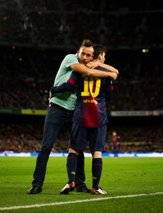 A pitch invader embraces Lionel Messi of Barcelona during the la Liga match between FC Barcelona and Club Atletico de Madrid at the Camp Nou