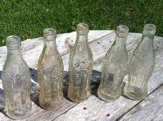 5 Bouteilles Coca-Cola des années 1930 embossées The Coca-Cola  Company of Canada Limited  - Trade Mark Registered min. contents 6-FL. OZS. : 9 triangle 37 - goulot brisé -  D dans un losange 38 - intact -  C dans un triangle 7 A 1934 - un chip au goulot -  C dans un triangle 8 A 1934- un chip au goulot C dans un triangle 9 A 1934 - un chip au goulot -   : 2$ à 10$ selon l'état