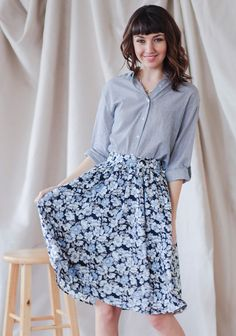 This navy skirt features a gorgeous floral print in pale shades of blue, gray, and white. Created with a partially elasticized waist, flowing silhouette and a hem that hits just at the knee, this...
