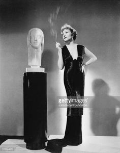 French born actress Claudette Colbert stands next to a sculpture smoking a cigarette.