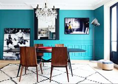 Vibrant turquoise dining space with dark wood table and chairs, a chandelier, diamond patterned area rug, and large framed photos.
