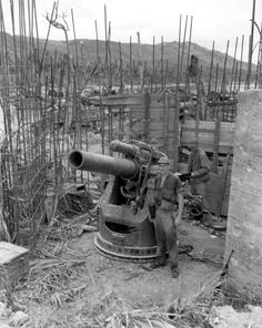 American soldiers next to a Japanese 200mm coastal defense gun, captured on Guam. The reinforced concrete fotification for the gun was unfinished.
