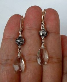 "Striking clear, crystal Quartz earrings with decorative 8mm Balinese silver balls and sterling silver hardware. The earrings have a total length of 2"". Design Theory Price $29 http://www.thedesigntheory.com 