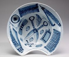 """1700-1720 British Shaving bowl in Historic Deerfield, Deerfield - From the curators' comments: """"Ceramic shaving bowls display a fairly consistent form: usually an oval or circular shape with a deep bowl and wide rim, often with a round depression for a soap ball, and a curved indentation for a man's throat....A ball of soap would be placed into the depression on the rim, and the barber would mix soap and water into a lather while the customer held the basin to his throat."""""""