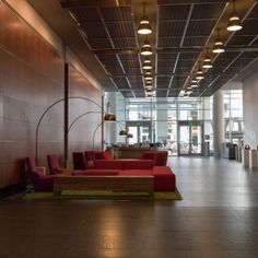 Office Building Entrance - Waiting area in an office building's foyer, with sofas and arc floor lamps.
