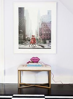 """A single oversized framed photograph anchors this entryway vignette with style. Love the gold-legged stool paired with the horizontal stack of styled coffee table books, glittery pink lips phone, and the pink of the fashion girls' street style in the image above. Get more interior design inspiration, ideas for creating the gallery wall of your dreams and more in """"Chic Ways to Decorate with Fashion Prints"""" on the One Kings Lane Style Guide!"""
