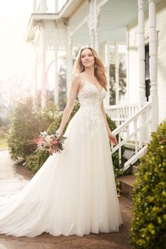 Style 822  An illusion lace bodice is the hallmark of this flirty A-line wedding gown from Martina Liana. The tulle skirt catches the light with your choice of ivory or white beading. The back zips up under pearl buttons.