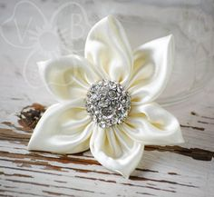 """""""White Christmas"""" is a white satin 6 point snowflake with a sparkly jeweled center, in the same design as our """"daffodil"""" clip. Elegant & simple, this accessory is great for holidays, weddings, or year-round wear! This hair accessory is secured to an alligator clip for easy we..."""