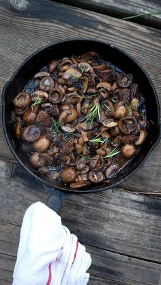 mushrooms in a cast iron pan, cooked over a fire