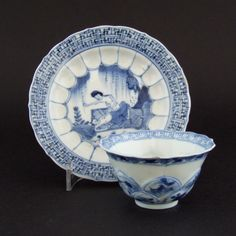 A Kangxi Blue and White Porcelain Teabowl and Saucer c.1700. The Moulded Body Decorated with an Erotic Scene of a Scantly Clad Couple Together Below a Willow Tree. KANGXI 1662 - 1722 Chinese Taste Porcelain (.) A Kangxi Blue and White Porcelain Teabowl and Saucer c.1700. The Moulded Body Decorated with an Erotic Scene of a Scantly Clad Couple Together Below a Willow Tree.