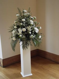 Classic plinth styling with a traditional theme floral arrangement n Ivory and white