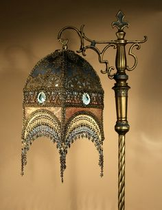 """A tall, gothic-inspired bridge lamp with a """"Rocket Ship"""" shaped shade lined with blue silk,  covered with gold metallic textiles, then overlaid with velvet appliqués; the 'waistband' of the shade sports a  faceted glass jewel (one on each of the four sides) embedded into the frame of the shade. Hand-beaded fringe hangs from the bottom edge of the shade."""
