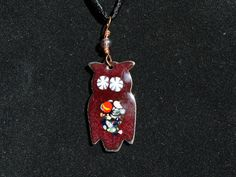 This whimsical owl was made by fusing powdered glass onto the stamped copper blank in a kiln at 1500 degrees. This owl is a lovely reddish brown color with white flower eyes, and a multi-colored speckled/swirled belly. The pendant is finished with a light purple bead on a hand twisted copper bail. The owl itself is about 1 1/4 high by 5/8 at the widest. The pendant, including the bail is about 1 7/8 long.  The necklace is made of silky black rayon cord with a hook and eye...