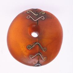 """African amber bead showing careful and decorative repair..."""
