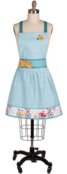 "This charming ""Enjoy The Ride"" Apron features a gathered blue and white horizontal thin striped skirt; and a 4-inch decorative skirt border. The border is accented with red, blue and yellow bicycles, and the phrases 'enjoy the ride' and 'life is beautiful;' and the top and bottom of border is trimmed in solid blue. Measures 26"" x 27"""