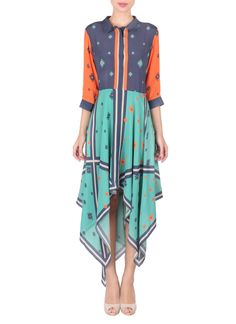 Asymmetric lines, candy colours and ruffles come together in this uber cool dress by Sougat Paul. With a prim blue shirt-like bodice, complete with a collar, orange sleeves and cuffs, this dress exudes an alluring appeal. It features a concealed button placket that runs in the front, up to the waist. The highlight of the outfit is its asymmetrically cut skirt.