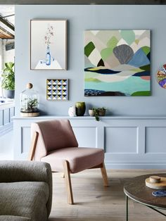 Light blue walls, colourful art and pink armchair