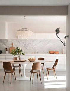 Mesa Saarinen, o painel com grandes pedras de mármore e o lustre de madrepérola. Para completar, a luminária industrial e a torneira clara na pia deixam o espaço ainda mais cool.  Fotografia: Reprodução.