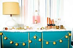 Neat display for holidays treats on a teal dresser with geometric stringed garland // via Emily Henderson, Photo by Jayme Burrows