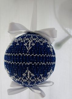 This handmade ornament is hand smocked and decorated with a white satin bow. Lovely ornament suitable for gift-giving! Presented in box with ribbon and gift tag. Also surprise bonus gift is included with order.