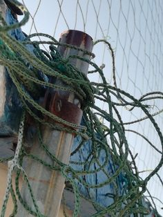 rope, fishing net, nautical vessel, fishing industry, transportation, mode of transport, boat, strength, tied up, fishing equipment, safety, outdoors, no people, moored, tangled, day, buoy, fishing tackle, sky, clear sky, complexity, harbor, sea, close-up