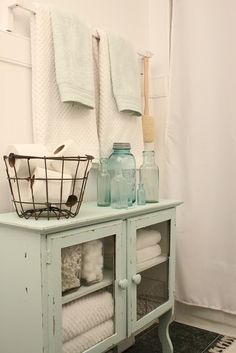 This bathroom storage area is shabby chic, rustic and perfect. The colors, the antique decor, the distressed wood