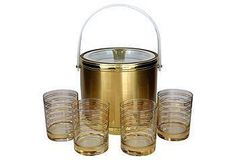 Midcentury gold-toned ice bucket paired with four gold-banded old fashioned glasses.
