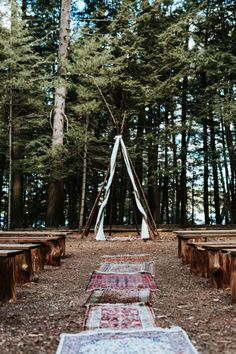 Lovely bohemian outdoor ceremony with Persian rugs and a teepee-inspired arbor | Image by Laura Rowe Photography and Kayla Rocca Photography